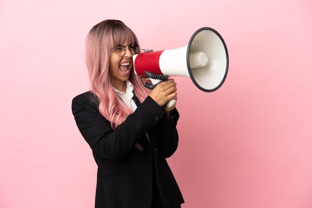 Молодая деловая женщина смешанной расы с розовыми волосами, изолированная на розовом фоне, кричит в мегафон