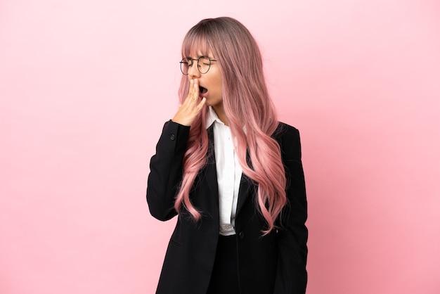 Молодая деловая женщина смешанной расы с розовыми волосами изолирована на розовом фоне, зевая и прикрывая широко открытый рот рукой