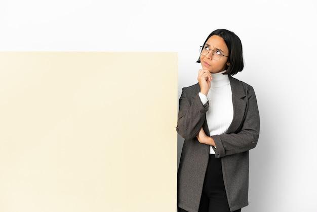 孤立した背景と見上げる大きなバナーと若いビジネス混血の女性