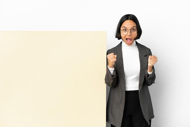 Молодая деловая женщина смешанной расы с большим баннером на изолированном фоне празднует победу в позиции победителя