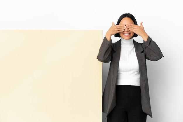 Молодая деловая женщина смешанной расы с большим знаменем на изолированном фоне, закрывающая глаза руками и улыбаясь