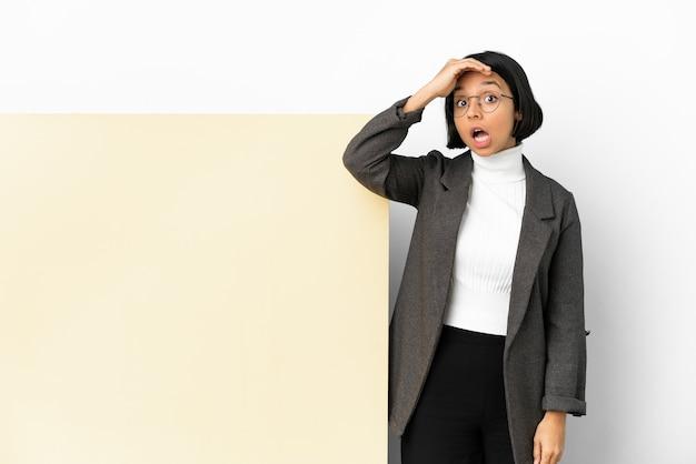 Молодая деловая женщина смешанной расы с большим баннером на изолированном фоне делает неожиданный жест, глядя в сторону