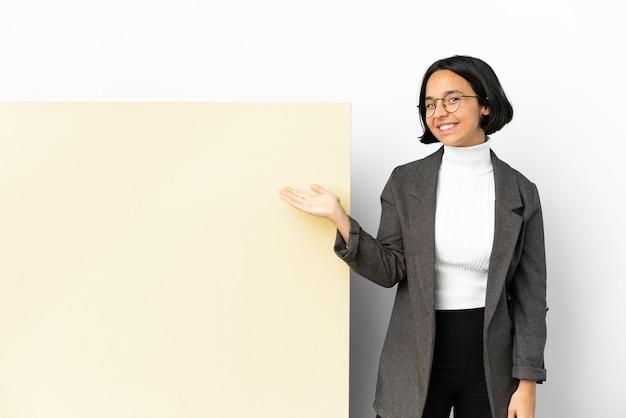 Молодая деловая женщина смешанной расы с большим баннером на изолированном фоне, протягивающая руки в сторону для приглашения приехать