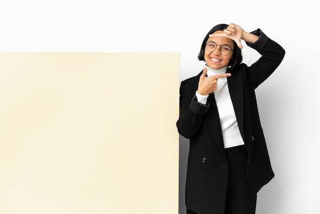 孤立した背景に焦点を当てた顔の上に大きなバナーを持つ若いビジネス混血の女性。フレーミングシンボル
