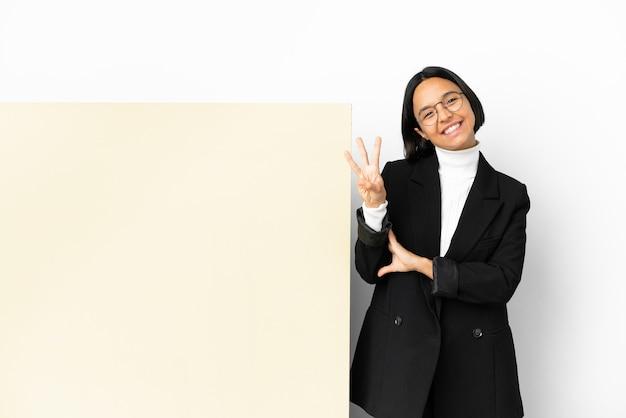 孤立した背景の上に大きなバナーと幸せな若いビジネス混血の女性と指で3を数える