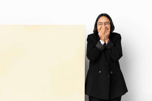 孤立した背景の上の大きなバナーと幸せで笑顔の手で口を覆う若いビジネス混血の女性