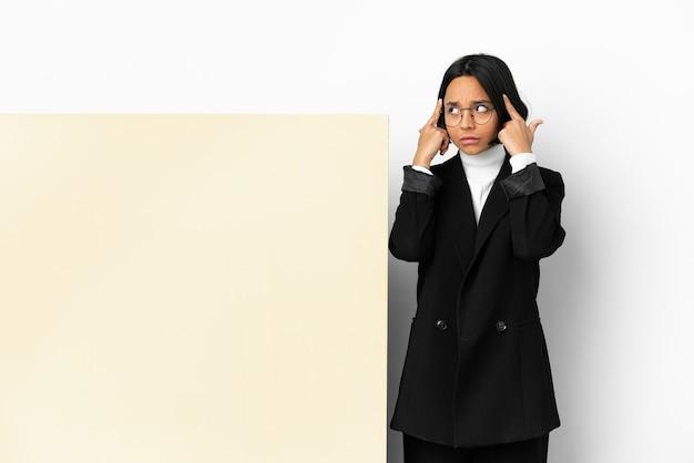 Молодая деловая женщина смешанной расы с большим знаменем на изолированном фоне с сомнениями и мышлением