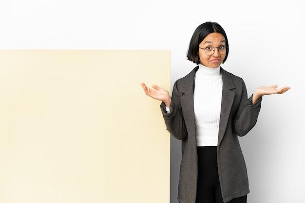 Молодая деловая женщина смешанной расы с большим знаменем на изолированном фоне, сомневающаяся, поднимая руки