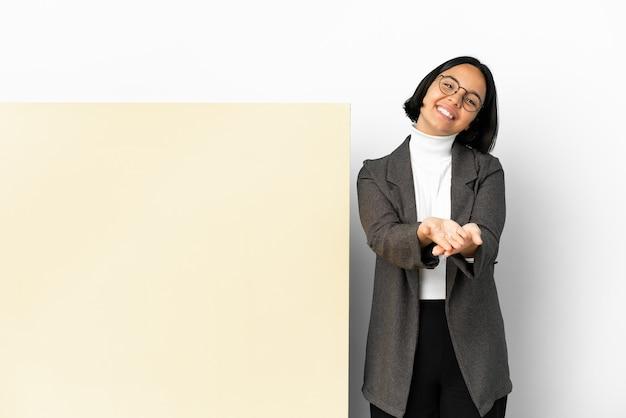광고를 삽입하기 위해 손바닥에 가상의 카피스페이스를 들고 고립된 배경 위에 큰 배너를 가진 젊은 비즈니스 혼혈 여성
