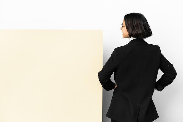 Молодая деловая женщина смешанной расы с большим баннером на изолированном фоне в заднем положении и смотрит в сторону