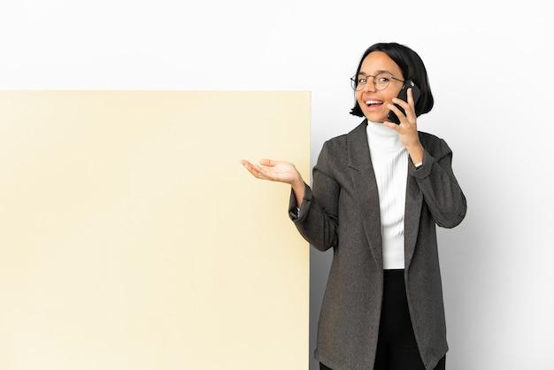 誰かと携帯電話との会話を維持している孤立した背景の上に大きなバナーを持つ若いビジネス混血の女性