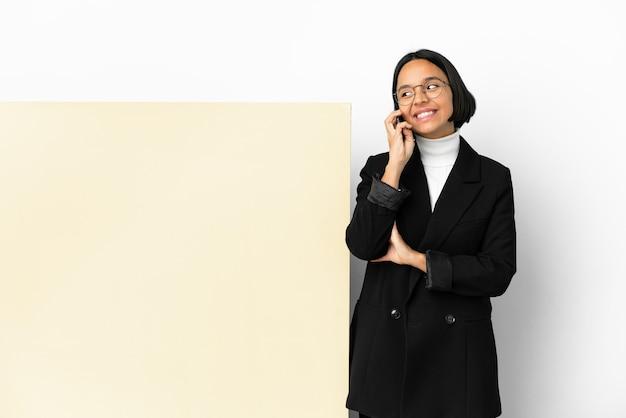 Молодая деловая женщина смешанной расы с большим баннером на изолированном фоне, поддерживающая разговор по мобильному телефону