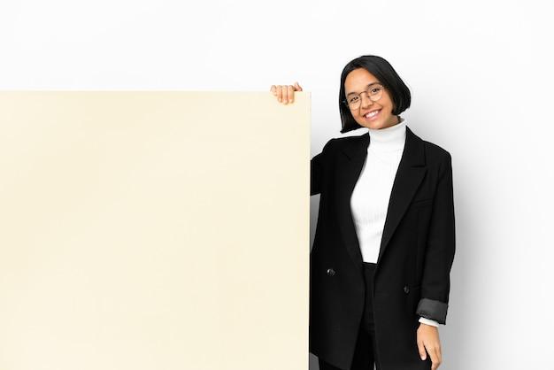 笑っている孤立した背景の上の大きなバナーと若いビジネス混血の女性