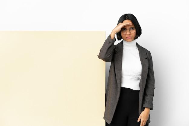 Молодая деловая женщина смешанной расы с большим знаменем на изолированном фоне смотрит вдаль с рукой, чтобы что-то посмотреть