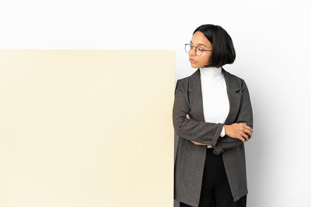 Молодая деловая женщина смешанной расы с большим баннером на изолированном фоне, глядя в сторону