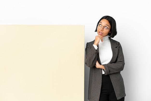 Молодая деловая женщина смешанной расы с большим знаменем на изолированном фоне, глядя вверх, улыбаясь