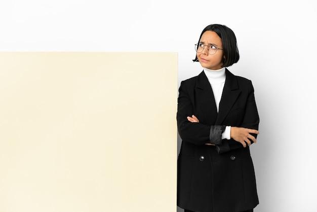 Молодая деловая женщина смешанной расы с большим баннером на изолированном фоне, делая жест сомнения, глядя в сторону