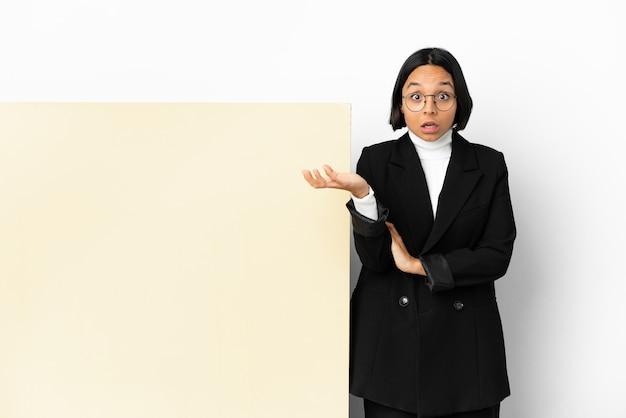 若いビジネス混血の女性と孤立した背景の上の大きなバナーで疑わしいジェスチャーを作る