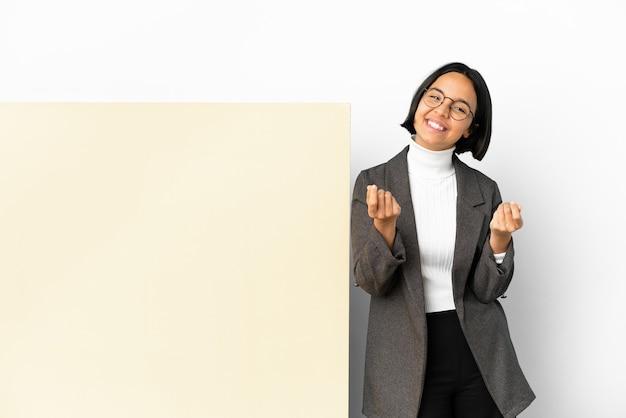 お金のジェスチャーを作る孤立した背景の上の大きなバナーと若いビジネス混血の女性
