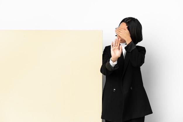 若いビジネス混血の女性と孤立した背景の上の大きなバナーで停止ジェスチャーを作成し、顔を覆う