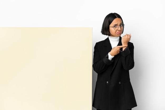 Молодая деловая женщина смешанной расы с большим баннером на изолированном фоне делает жест опоздания