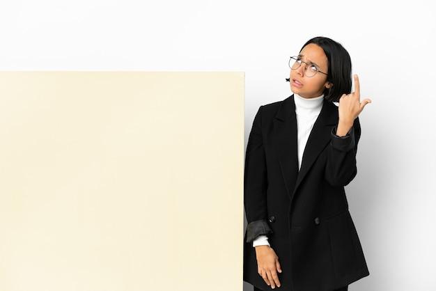 Молодая деловая женщина смешанной расы с большим знаменем на изолированном фоне делает жест безумия, положив палец на голову