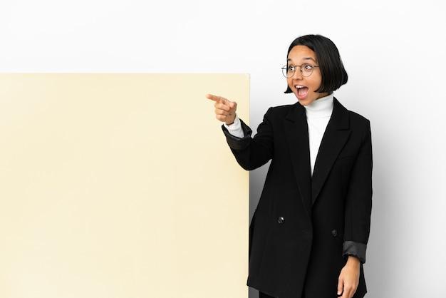 Молодая деловая женщина смешанной расы с большим знаменем на изолированном фоне, указывая в сторону