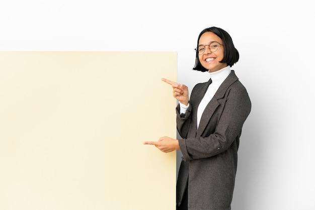 Молодая деловая женщина смешанной расы с большим баннером на изолированном фоне, указывая пальцем в сторону и представляя продукт