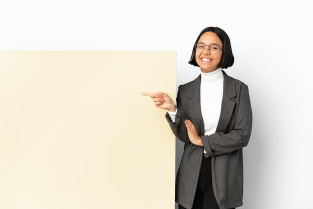 Молодая деловая женщина смешанной расы с большим знаменем на изолированном фоне, указывая пальцем в сторону