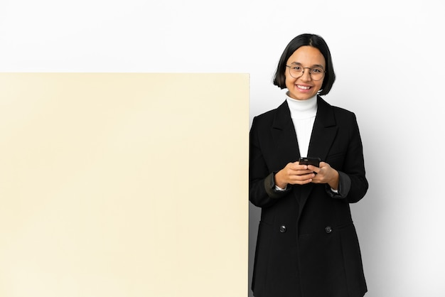 Молодая деловая женщина смешанной расы с большим баннером на изолированном фоне, отправив сообщение с мобильного телефона