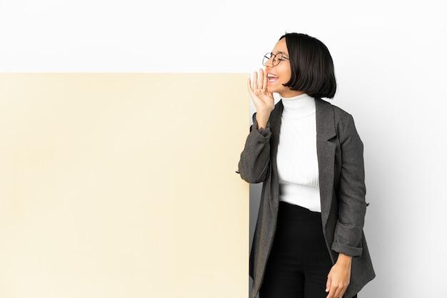 Молодая деловая женщина смешанной расы с большим знаменем на изолированном фоне кричит с широко открытым ртом в сторону