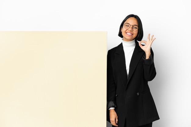 손가락으로 확인 표시를 보여주는 격리 된 배경 위에 큰 배너와 함께 젊은 비즈니스 혼혈 여자