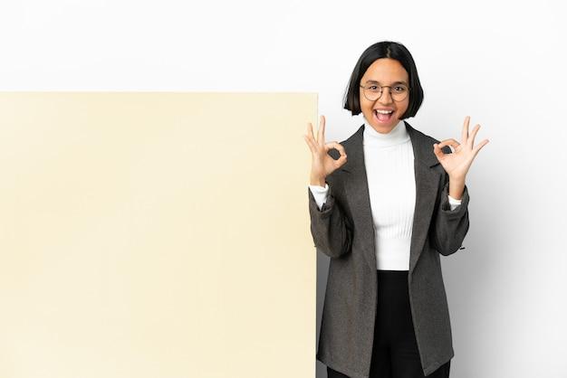 두 손으로 확인 표시를 보여주는 격리 된 배경 위에 큰 배너와 함께 젊은 비즈니스 혼혈 여자
