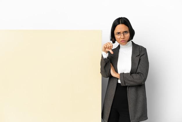 否定的な表現で親指を示す孤立した背景の上に大きなバナーを持つ若いビジネス混血の女性