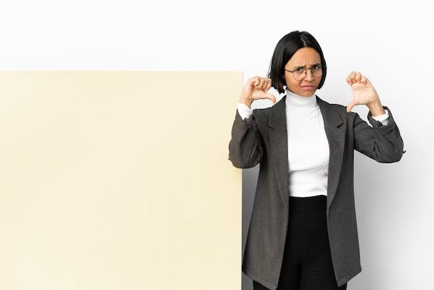 Молодая деловая женщина смешанной расы с большим баннером на изолированном фоне показывает большой палец вниз двумя руками