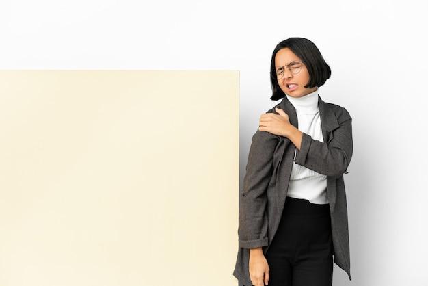 노력을 한 데 대한 어깨에 통증을 앓고 고립 된 배경 위에 큰 배너와 함께 젊은 비즈니스 혼혈 여자