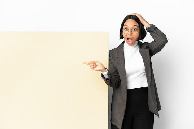 Молодая деловая женщина смешанной расы с большим знаменем на изолированном фоне удивлена и показывает пальцем в сторону