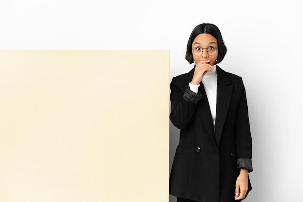 孤立した背景の上に大きなバナーを持つ若いビジネス混血の女性は、右を見ながら驚いてショックを受けました