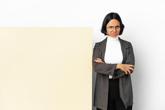 Молодая деловая женщина смешанной расы с большим знаменем на изолированном фоне с несчастным выражением лица