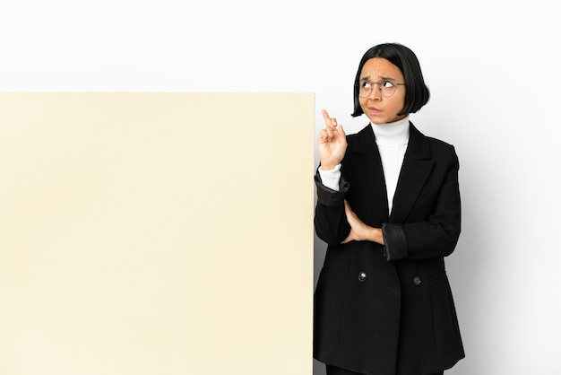 Young business mixed race woman with with a big banner over isolated background with fingers crossing and wishing the best
