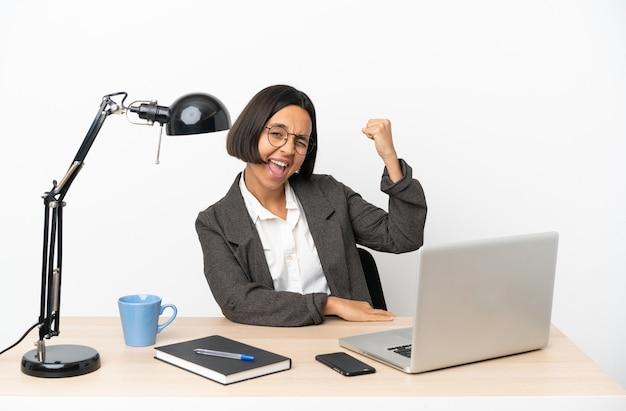 Молодая деловая женщина смешанной расы, работающая в офисе, празднует победу