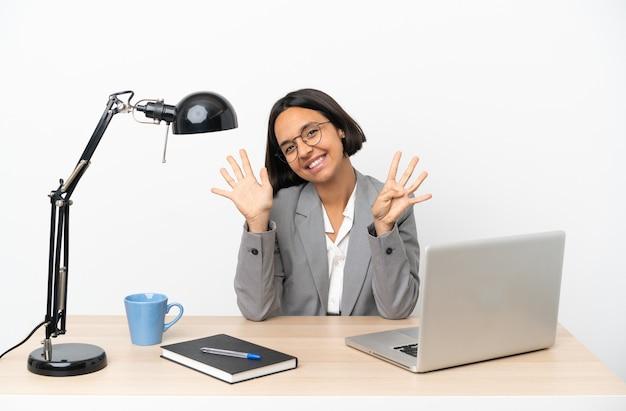 Молодая деловая женщина смешанной расы, работающая в офисе, считая девять пальцев