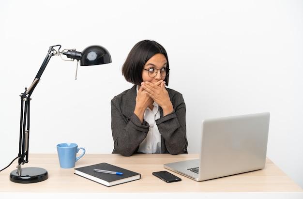 Молодая деловая женщина смешанной расы, работающая в офисе, прикрывая рот и глядя в сторону
