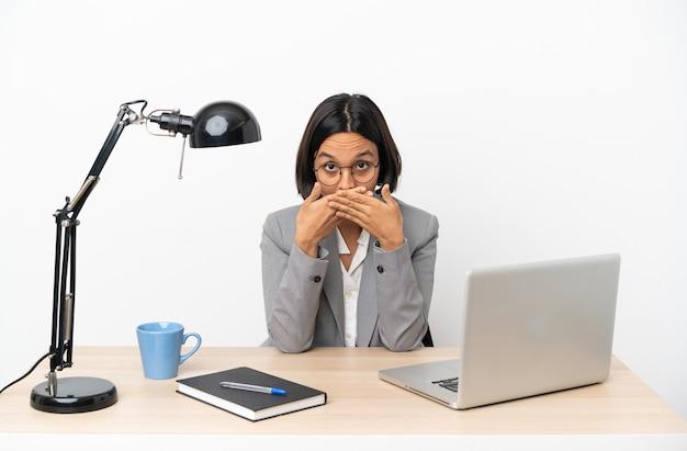 손으로 입을 덮고 사무실에서 일하는 젊은 비즈니스 혼혈 여자
