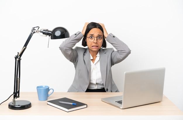 Молодая деловая женщина смешанной расы, работающая в офисе, делает нервный жест