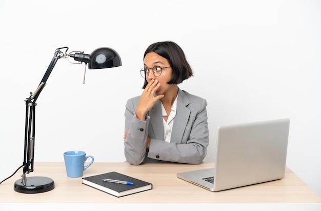 Молодая деловая женщина смешанной расы, работающая в офисе, делает неожиданный жест, глядя в сторону