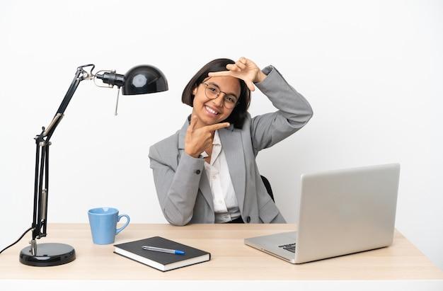 얼굴에 초점을 맞추고 사무실에서 일하는 젊은 비즈니스 혼혈 여자. 프레이밍 기호