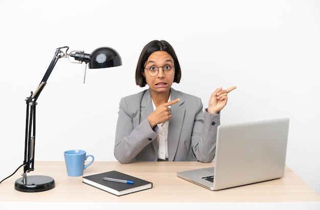 사무실에서 일하는 젊은 비즈니스 혼혈 여자가 두려워하고 측면을 가리키는