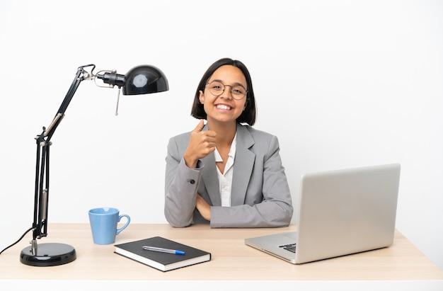 オフィスで働く若いビジネス混血女性が親指を立てるジェスチャーをする