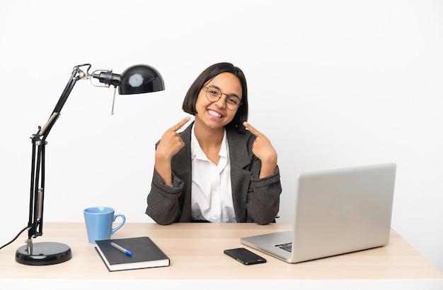 Молодая деловая женщина смешанной расы, работающая в офисе, показывает палец вверх